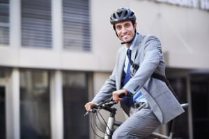 A businessman riding his bicycle to work in the city central while wearing a bicycle helmet