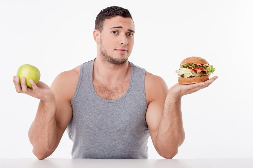 Handsome man chooses between healthy and unhealthy food