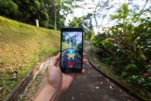 Man playing Pokemon Go with blur background