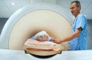 Mature radiologist consoling patient before MRI scan.