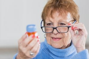 Senior woman reading directions on prescription bottle
