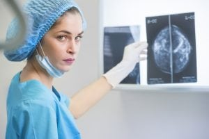 A doctor holds up a mammogram
